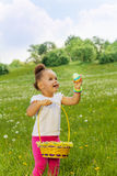 Positive small girl with eastern egg and basket Stock Photos
