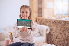 Positive smart girl using a banking app. Future financier. Positive smart girl smiling while using a banking app Royalty Free Stock Photography