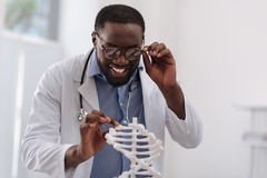 Positive smart man touching the DNA model Stock Photography