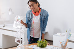 Positive smart student touching the gene model. Modern genomics. Positive smart curious student standing near the gene model and touching it while studying royalty free stock photography