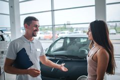 Positive and smileful man stand and point on black car. He looks at young woman. She is listening to him. Model is calm royalty free stock photography
