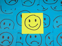 Positive smiley face on sticky note. Over sad faces Royalty Free Stock Images