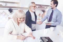 Positive smilign aged woman signing insurance contract. Well done. Cheeful delighted women signing insurance contract while her husband shaking hands with agent stock photography