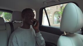 Positive, smiling african man in casual clothes talking on cellphone while riding in backseat of taxi cab. Cheerful