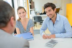 Positive smiling agent explaining details contract young couple stock photography