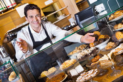 Positive smiling cafe staff offering fancy and sponge cakes. For sale Royalty Free Stock Image