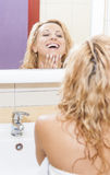 Positive and Smiling Caucasian Blond Woman Looking in Mirror and Examining Her Face Royalty Free Stock Photos