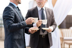 Positive smiling colleagues drinking coffee. Favorite beverage. Cheerful delighted smiling colleagues talking and drinking coffee while expressing gladness royalty free stock image