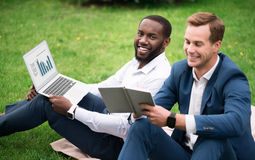 Positive smiling colleagues sitting on the grass. Full of gladness. Pleasant cheerful smiling colleagues using laptop and sitting on the grass while working on Stock Photos