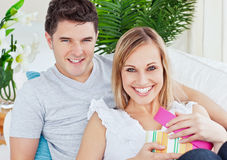 Positive smiling couple with woman opening present. Beautiful couple smiling at the camera while woman unwrap a present lying on the sofa at home Stock Photography