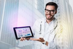 Positive smiling doctor pointing to the screen of a tablet Royalty Free Stock Image