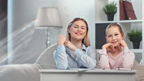 Positive smiling family mother and daughter posing on table enjoying break during making homework. Positive smiling young family mother and daughter posing on stock video footage