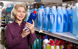 Positive smiling female with selecting fabric conditioner Royalty Free Stock Photos