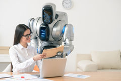 Positive smiling girl getting package from the robot Stock Image
