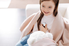 Positive smiling girl playign with her fluffy toy Stock Images