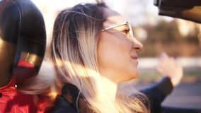 Positive, smiling, long haired girl in transparent sunglasses driving her cabriolet car in the city. Young woman stock video footage