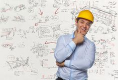 Positive smiling male in white shirt and hard yellow cap. Positive smiling male in white shirt and hard yellow cap over white desk with drawnings Stock Images