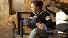 Positive and smiling mama feeding baby outdoor on a bench having rest stock images