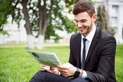 Positive smiling man sitting on the grass Stock Photo