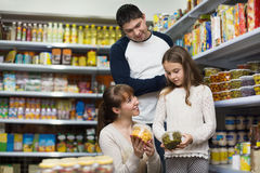 Positive smiling parents with little girl buying tinned Stock Photo