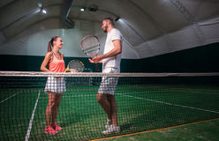 Positive smiling professioanl tennis players talking. Involved in talk. Positive delighted tennis players holding rackets and talking while standing in indoor Stock Photography