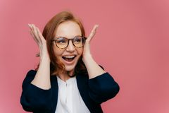 Positive smiling redhead woman covers ears, happy to hear something noisy and funny, wears transparent glasses, black and white. Elegant clothes, stands over royalty free stock images
