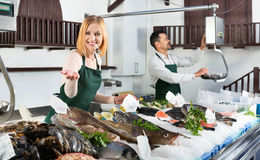 Positive smiling  shop assistants selling fresh fish Stock Photo