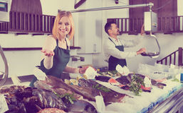 Positive smiling shop assistants selling fresh fish. And chilled seafood stock photography