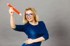 Smiling woman holds big pencil in hand royalty free stock images