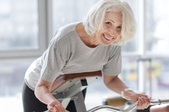 Positive smiling woman doing exercising with easy bar. Stock Images