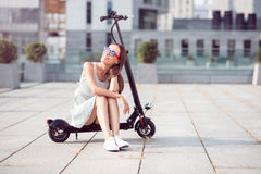 Positive smiling woman riding a kick scooter. Have a break. Joyful beautiful woman smiling and sitting on the kick scooter while resting Royalty Free Stock Photos