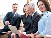Positive smiling woman sitting with her colleagues Royalty Free Stock Photo