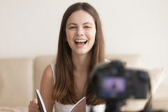Positive smiling woman talking on camera, recording book review. Positive woman talks on digital camera advertising product from catalog when recording videoblog Stock Photos