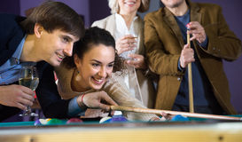 Positive smiling young couple playing pool in billiards Royalty Free Stock Images