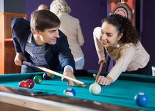 Positive smiling young couple playing pool looking at each other Royalty Free Stock Photos