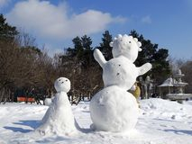Positive snowmen. Sculpt snowmen - Russian winter children`s game Stock Photos