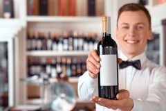 Positive sommelier holding wine bottle Stock Image