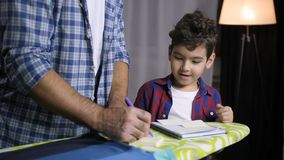 Positive son and dad learning together at home stock footage