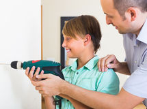Positive son helping proud father to drill Stock Images
