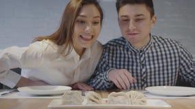 Positive Spaßpaare des Porträts, die mit Interesse auf Mehlklöße khinkali auf dem Tisch steht vor ihnen nah oben schauen stock video footage