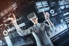Positive specialist changing setting while being in virtual reality. Changing settings. Excited young smart programmer wearing virtual reality glasses and Royalty Free Stock Images