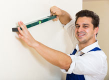 Positive specialist making wall plane in new building Royalty Free Stock Image