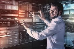 Positive specialist smiling cheerfully while working with modern technologies. Feeling glad. Emotional young experienced programmer standing next to a futuristic Royalty Free Stock Images