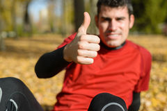 Positive sportsman. With thumbs up. Approving concept with hand in foreground and cheerful athlete on background outside in park Stock Photo