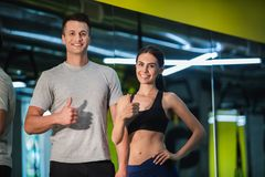 Positive sporty couple is expressing like gesture indoors stock photos
