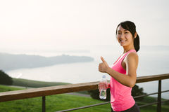 Positive sporty woman doing thumbs up gesture. Positive happy female athlete taking a workout break for drinking water. Asian woman on a training rest towards Royalty Free Stock Photos