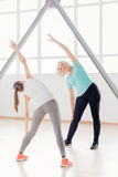 Positive sporty women doing bending exercises. Exercising together. Positive sporty active women holding their arms up and bending to the right while having Stock Photography