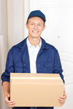 Positive standing near the door. Best service. Positive upbeat deliverymen waiting near the door and holding box while delivering it royalty free stock photography