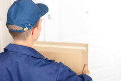 Positive standing near the door. Parcel for you. Pleasant professional deliveryman holding box and standing near window while waiting royalty free stock images