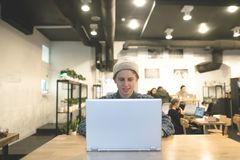 A positive student enjoys a laptop in a cozy cafe. The stylish hipsters work at the computer at the cafe. A positive student enjoys a laptop in a cozy cafe Stock Image